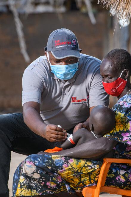 Ein Mann mit Johannitershirt misst den Oberarm eines Kindes das bei seiner Mama auf dem Schoß sitzt. Alle tragen einen Mund-Nasen-Schutz