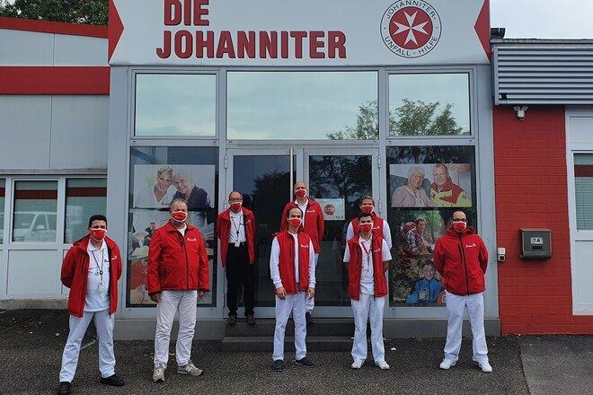 Acht Menschen in Johanniter-Kleidung vor der Johanniter-Dienststelle Solingen