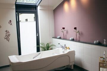 Eine große Badewanne im schön gestalteten Badezimmer des Hospizes
