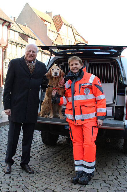 Ein Mann, eine Johanniterin in Einsatzkleidung stehen vor einem Auto. Der Kofferraum ist geöffnet und im Laderaum steht ein Hund