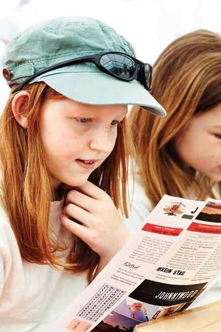 Ein Mädchen liest in einer Zeltlager-Zeitung