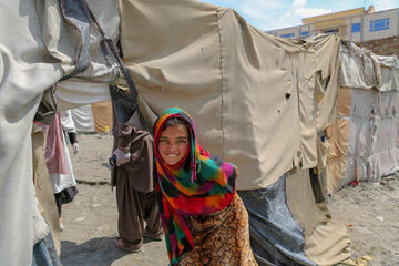 A girl stands in front of a provisional shelter in one of Kabul's informal settlements