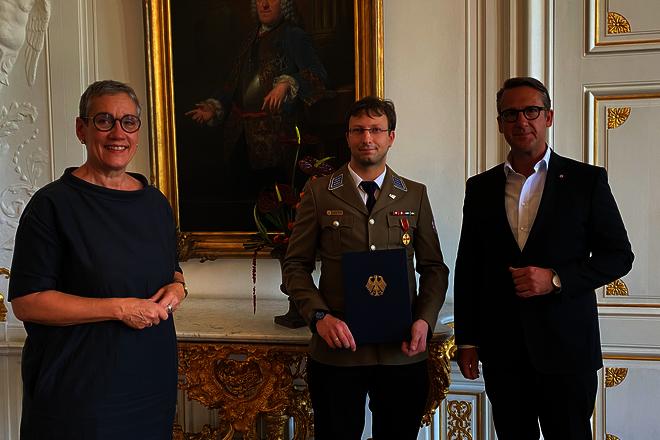Eine Frau und zwei Männer stehen im weißen Saal des Aachener Rathaus. In der Mitte Jend von den Berken in einer Dienstbekleidung der Johanniter und mit Auszeichnungen.