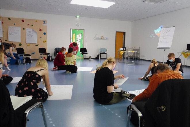 Mitarbeitende sitzen verteilt im Bewegungsraum und schreiben ihre Fragen und Gedanken auf große Plakate.