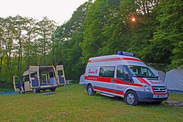 Zwei Johanniterautos stehen auf einer Wiese mit offenem Kofferraum und es wird Zeltmaterial entladen