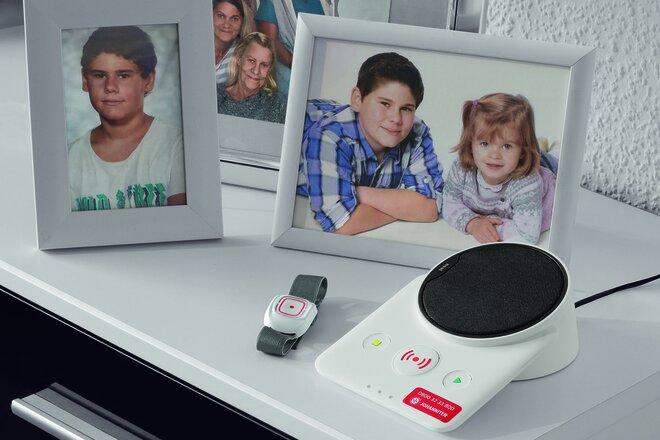 Eine Hausnotrufbasisstation steht neben Familienfotos auf einer weißen Anrichte