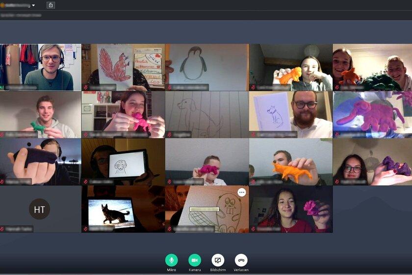 Screenshot einer Videokonferenz, bei der die Teilnehmer:innen verschiedene Tiere aus Knete in die Kamera halten.