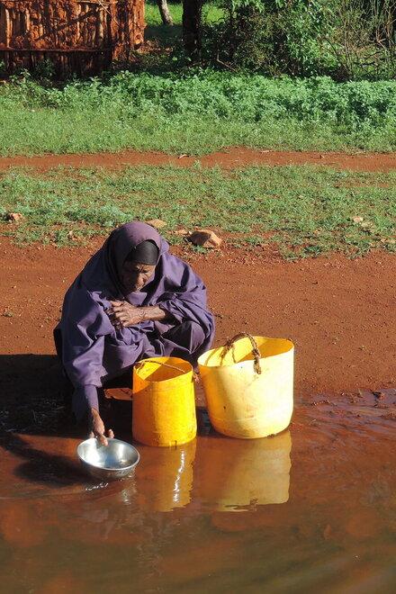 Eine ältere Dame schöpft Wasser aus dem Fluss, dessen Wasser braun ist