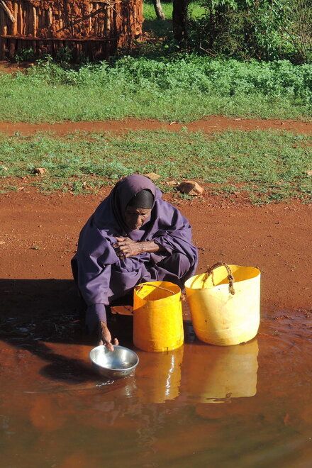 An elderly lady draws water from the river, which has brown water