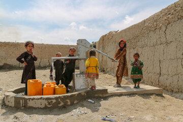 Kinder stehen um einen Trinkbrunnen herum