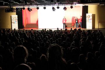 Eine Aula mit vielen Menschen, die Bühne vorne ist beleuchtet und Personen in Johanniter-Jugend-Kleidung reden.