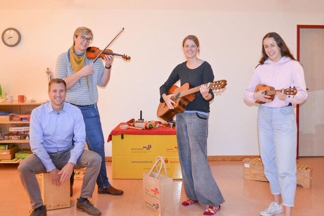 Florian Friedrich (Sparkasse), Annika Holmer (Leitung Johanniter-Kinderhaus Wilde 13), Mareike Irsigler und Emely Burchardt (musiculum MOBIL) zeigen die mitgebrachten Instrumente.