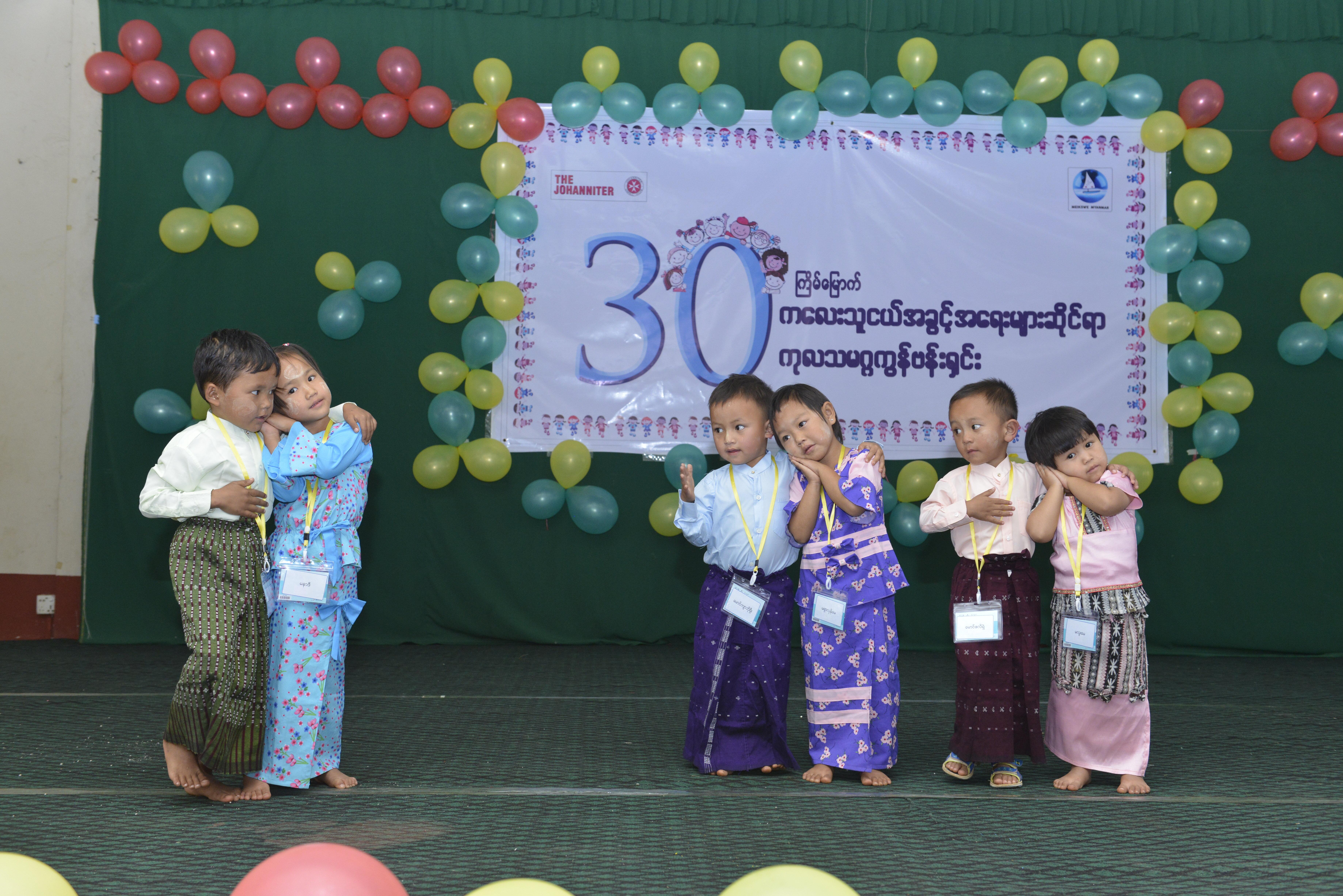 Kinder spielen vor einem Banner der Johanniter