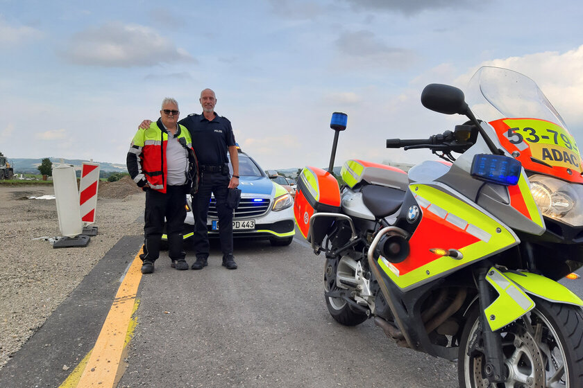 Ein Johanniter-Motorradstaffel-Mitglied und ein Polizist mit Krad und Einsatzwagen auf der Autobahn