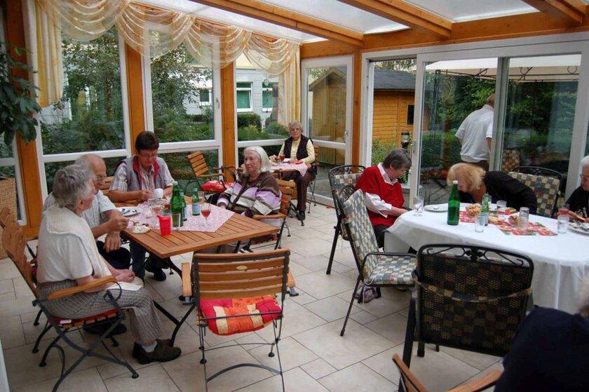 Die Senioren sitzen an Tischen im lichtdurchfluteten Wintergarten der Tagespflege und unterhalten sich.