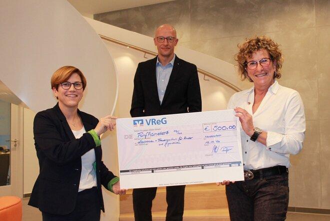 Jens-Hartwig Göttsch (Bereichsleiter VReG Region Norderstedt) und Kathleen Röpke (Mitarbeiterin Marketing VReG) überreichen der ehrenamtlichen Johanniterin Bettina Schröder den Spendenscheck.
