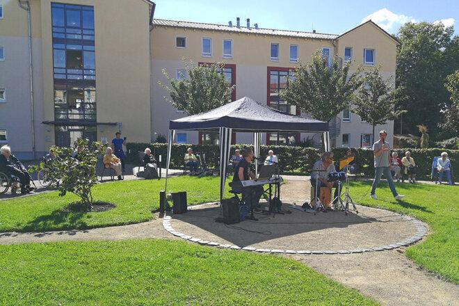 Musiker mit Kiboard und Mikrofone spielen zahlreiche Lieder auf der Wiese. Mit großem Abstand sitzen die Zuhöhrenden im Kreis um die Band herum.