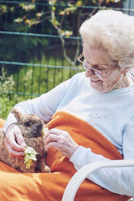 Eine Bewohnerin sitzt im Garten und streichelt Kaninchen