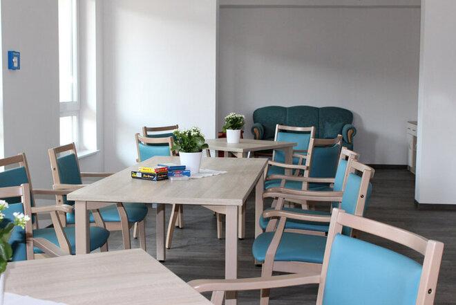 Blick in den Gemeinschaftsraum mit seinen Tischen und gemütlichen blauen Stühlen.
