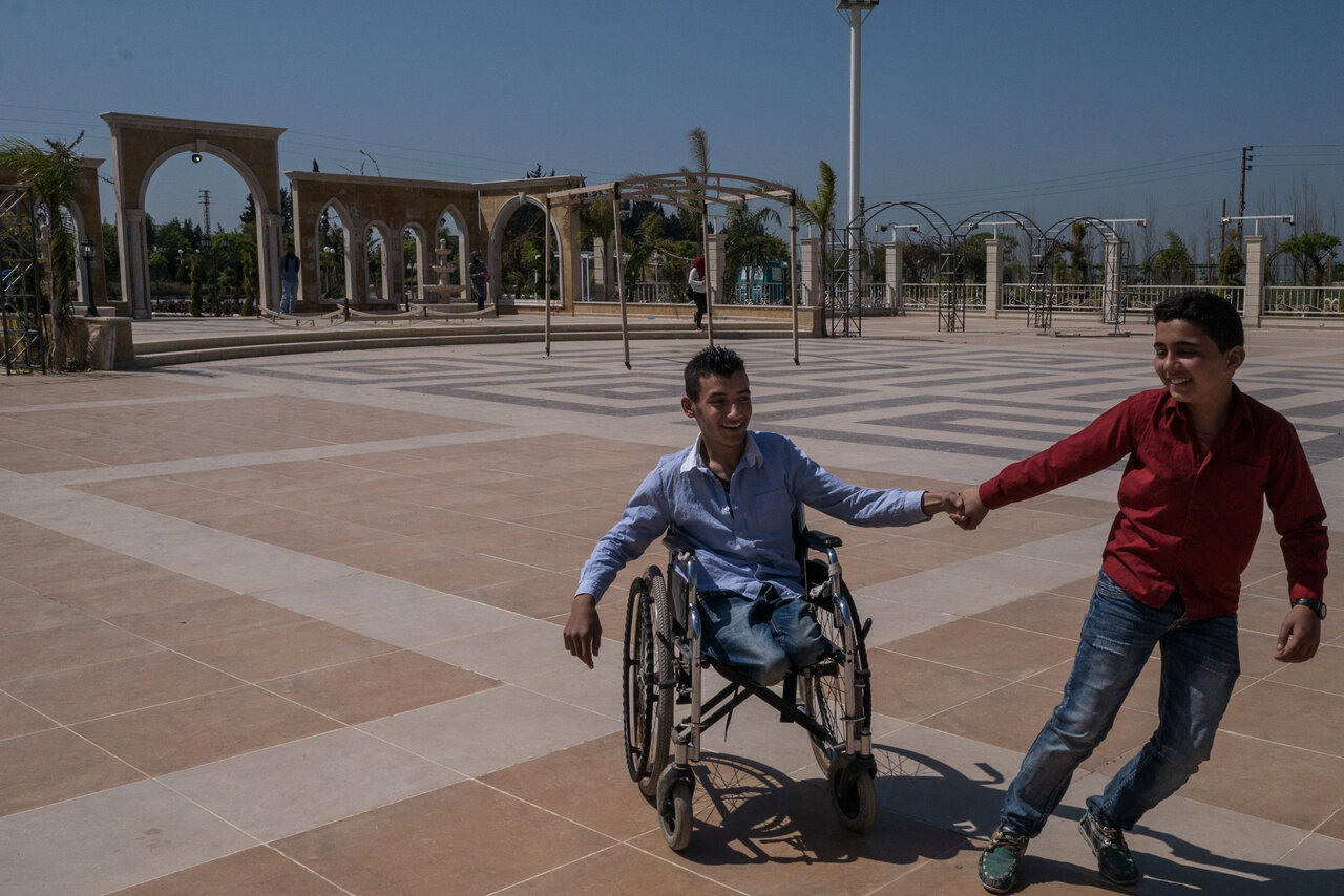 A boy plays with another boy who is in a wheelchair