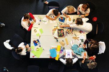 Kinder basteln an einem Tisch, Aufnahme von oben