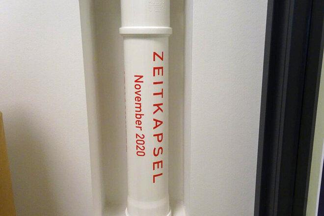 Zeitkapsel in weiß mit Name der Kita und Datum.