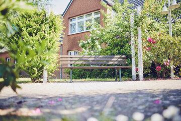 Gartenbank zwischen zwei kleinen Bäumen laden zum Entspannen ein