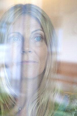 Frau hinter einer Glasscheibe