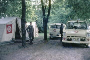 Sanitäter und Fahrzeuge vor einem Sanitätszelt im Jahr 1964.