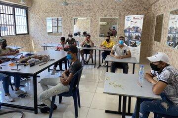 Jugendliche mit Mund-Nasen Bedeckung sitzen in einem Klassenzimmer