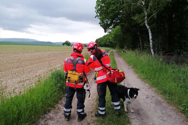 Zwei Hundeführerinnen stehen gemeinsam mit einem Rettungshund am Waldrand.
