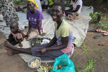 A smiling women is sitting on the floor next to ingridients for cooking