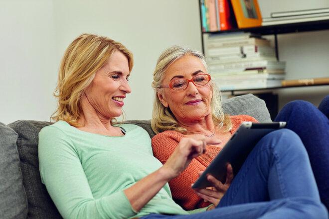 Eine jüngere und eine ältere Frau bedienen schauen auf ein Tablet.