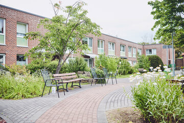 Gartenbänke stehen in der gepflegten Anlage des Johanniter-Stift Gut Heuserhof in Köln.