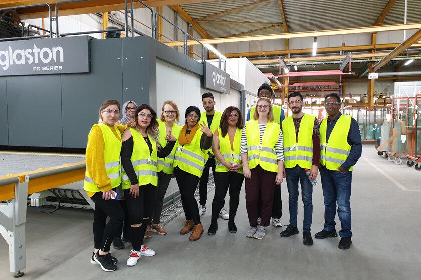 Teilnehmende der Erstorientierungskurse und ihre Lehrkräfte stehen in der Produktionshalle der Interpane Glasindustrie AG.