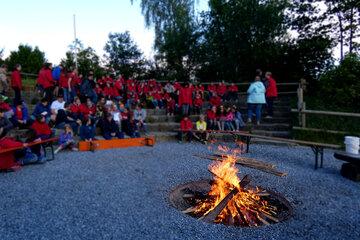 Viele Menschen in Johanniter-Jugend-Kleidung sitzen mit Abstand um ein Lagerfeuer.